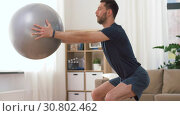 Купить «man exercising and doing squats with ball at home», видеоролик № 30802462, снято 15 мая 2019 г. (c) Syda Productions / Фотобанк Лори