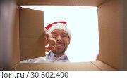 Купить «happy man opening parcel box or christmas gift», видеоролик № 30802490, снято 15 мая 2019 г. (c) Syda Productions / Фотобанк Лори