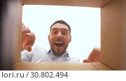 Купить «happy man opening parcel box», видеоролик № 30802494, снято 15 мая 2019 г. (c) Syda Productions / Фотобанк Лори