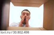 Купить «happy man opening parcel box», видеоролик № 30802498, снято 15 мая 2019 г. (c) Syda Productions / Фотобанк Лори
