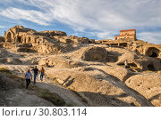 Tourists visit the ancient cave city Uplistsikhe, a popular tourist attraction in Georgia (2018 год). Редакционное фото, фотограф Юлия Бабкина / Фотобанк Лори
