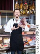 Купить «Positive man seller showing piece of meat», фото № 30809078, снято 2 января 2017 г. (c) Яков Филимонов / Фотобанк Лори