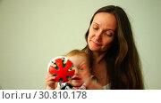 Купить «The baby plays a-round toy next to her mother», видеоролик № 30810178, снято 4 ноября 2017 г. (c) Aleksandr Sulimov / Фотобанк Лори