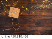 mockup Christmas kraft gift box with xmas garland on wooden background. Top view for greeting card with place for text. Стоковое фото, фотограф Happy Letters / Фотобанк Лори