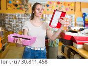 Купить «Young female is choosing red or pink palettes for trifle», фото № 30811458, снято 19 апреля 2017 г. (c) Яков Филимонов / Фотобанк Лори