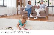 Купить «adults talking and girl drawing at home», видеоролик № 30813086, снято 12 мая 2019 г. (c) Syda Productions / Фотобанк Лори