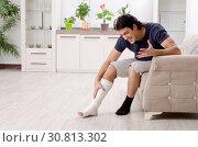Купить «Leg injured young man suffering at home», фото № 30813302, снято 15 января 2019 г. (c) Elnur / Фотобанк Лори