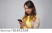 Купить «asian woman using smartphone», видеоролик № 30813534, снято 17 мая 2019 г. (c) Syda Productions / Фотобанк Лори