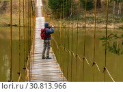 Woman traveler takes a picture from a suspension bridge over the spring river. Стоковое фото, фотограф Евгений Харитонов / Фотобанк Лори