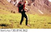 Купить «Hiking man walking on green mountain meadow with backpack. Summer sport and recreation concept.», видеоролик № 30814362, снято 17 апреля 2018 г. (c) Александр Маркин / Фотобанк Лори