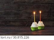 Купить «birthday cupcakes with candles on old dark wooden background», фото № 30815226, снято 14 марта 2019 г. (c) Майя Крученкова / Фотобанк Лори