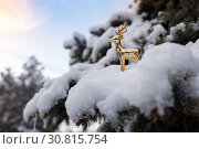 Купить «Golden toy deer stands on a snowy branch of evergreen pine on background blue sky», фото № 30815754, снято 16 января 2019 г. (c) Олег Белов / Фотобанк Лори