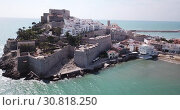 Купить «Picturesque aerial view of coastal line of Spanish tourist town of Peniscola with medieval castle on crag», видеоролик № 30818250, снято 16 апреля 2019 г. (c) Яков Филимонов / Фотобанк Лори