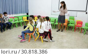 Купить «Happy kids and female teacher playing musical chairs together during break in classroom at elementary school», видеоролик № 30818386, снято 30 января 2019 г. (c) Яков Филимонов / Фотобанк Лори