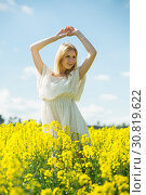 Купить «Young woman in yellow oilseed rape field stretch oneself outdoor», фото № 30819622, снято 8 апреля 2019 г. (c) Яков Филимонов / Фотобанк Лори
