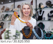 Купить «Woman trying on a aventurine necklace and earrings at a jewelry store», фото № 30820950, снято 2 мая 2019 г. (c) Яков Филимонов / Фотобанк Лори