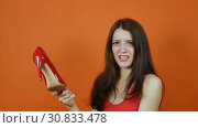 Купить «A beautiful young brown-haired girl examines a pair of red shoes. Emotions. Art portrait in a studio on an orange background», видеоролик № 30833478, снято 8 апреля 2019 г. (c) Ольга Балынская / Фотобанк Лори