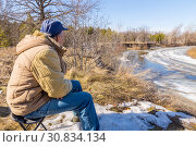 Купить «Spring landscape. Tourist watching the movement of ice on the river.», фото № 30834134, снято 11 апреля 2018 г. (c) Акиньшин Владимир / Фотобанк Лори