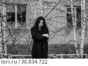 Купить «Young woman at the background of an abandoned house», фото № 30834722, снято 26 мая 2019 г. (c) Art Konovalov / Фотобанк Лори