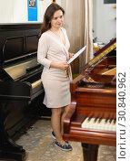 Купить «Pretty saleswoman in piano record store», фото № 30840962, снято 16 апреля 2019 г. (c) Яков Филимонов / Фотобанк Лори
