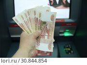 In the hand of 55 thousand rubles in banknotes of five thousand rubles against the ATM. Moscow (2019 год). Редакционное фото, фотограф Ольга Зиновская / Фотобанк Лори