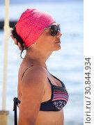 Купить «Портрет привлекательной загорелой женщины, одетой в купальник и красный платок, солнцезащитные очки на глазах, морской берег», фото № 30844934, снято 23 июля 2018 г. (c) Кекяляйнен Андрей / Фотобанк Лори