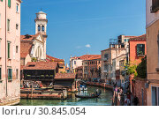 Купить «View of cityscape with colorful buildings on the banks of the canal and gondola with tourists, Venice, Italy», фото № 30845054, снято 23 апреля 2017 г. (c) Наталья Волкова / Фотобанк Лори