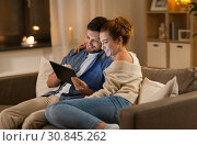 Купить «happy couple using tablet pc at home in evening», фото № 30845262, снято 5 января 2019 г. (c) Syda Productions / Фотобанк Лори