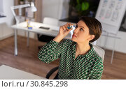 businesswoman using eye drops at night office. Стоковое фото, фотограф Syda Productions / Фотобанк Лори