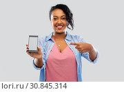 Купить «happy african american woman showing smartphone», фото № 30845314, снято 2 марта 2019 г. (c) Syda Productions / Фотобанк Лори