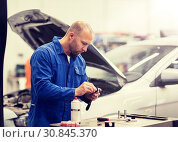 mechanic man with wrench repairing car at workshop. Стоковое фото, фотограф Syda Productions / Фотобанк Лори