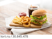 Купить «close up of fast food and cola drink on table», фото № 30845478, снято 21 мая 2015 г. (c) Syda Productions / Фотобанк Лори