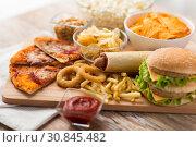 Купить «close up of fast food on wooden board», фото № 30845482, снято 21 мая 2015 г. (c) Syda Productions / Фотобанк Лори