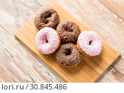 Купить «close up of glazed donuts pile on wooden board», фото № 30845486, снято 21 мая 2015 г. (c) Syda Productions / Фотобанк Лори