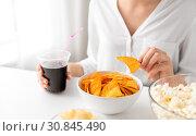 Купить «close up of woman eating corn nachos with cola», фото № 30845490, снято 21 мая 2015 г. (c) Syda Productions / Фотобанк Лори