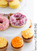 Купить «close up of glazed donuts and cupcakes on stand», фото № 30845542, снято 6 июля 2018 г. (c) Syda Productions / Фотобанк Лори