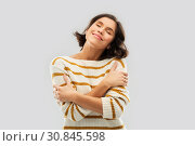 Купить «happy woman in striped pullover hugging herself», фото № 30845598, снято 6 марта 2019 г. (c) Syda Productions / Фотобанк Лори