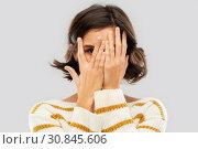 Купить «young woman looking by one eye through her fingers», фото № 30845606, снято 6 марта 2019 г. (c) Syda Productions / Фотобанк Лори