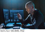 Купить «hacker with smartphone and computers in dark room», фото № 30845702, снято 9 ноября 2017 г. (c) Syda Productions / Фотобанк Лори