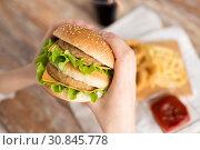 Купить «close up of woman holding hamburger», фото № 30845778, снято 21 мая 2015 г. (c) Syda Productions / Фотобанк Лори