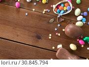 Купить «chocolate eggs, easter bunny and candies on wood», фото № 30845794, снято 22 марта 2018 г. (c) Syda Productions / Фотобанк Лори