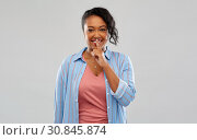 Купить «happy african american woman with finger on lips», фото № 30845874, снято 2 марта 2019 г. (c) Syda Productions / Фотобанк Лори