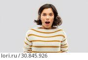 Купить «surprised young woman in striped pullover», фото № 30845926, снято 6 марта 2019 г. (c) Syda Productions / Фотобанк Лори