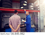 Купить «auto mechanic and man with tires at car shop», фото № 30845982, снято 1 июля 2016 г. (c) Syda Productions / Фотобанк Лори