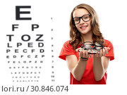 Купить «teenage girl holding glasses over eye test chart», фото № 30846074, снято 17 февраля 2019 г. (c) Syda Productions / Фотобанк Лори