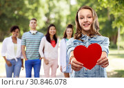 Купить «smiling teenage girl with red heart outdoors», фото № 30846078, снято 17 февраля 2019 г. (c) Syda Productions / Фотобанк Лори