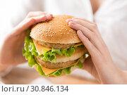 Купить «close up of woman holding hamburger», фото № 30846134, снято 21 мая 2015 г. (c) Syda Productions / Фотобанк Лори
