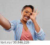 Купить «happy african american woman taking selfie», фото № 30846226, снято 2 марта 2019 г. (c) Syda Productions / Фотобанк Лори