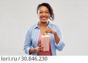 Купить «happy african american woman eating popcorn», фото № 30846230, снято 2 марта 2019 г. (c) Syda Productions / Фотобанк Лори