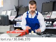 Купить «Male worker picking up color of car upholstery», фото № 30846370, снято 4 апреля 2018 г. (c) Яков Филимонов / Фотобанк Лори